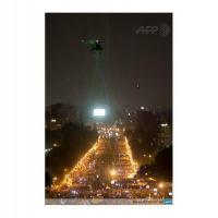 Um helicóptero AH-64 Apache das Forças Armadas do Egípcias sobrevoando os manifestantes na Praça Tahrir, Cairo, Egito, é iluminado por centenas de laser verde. Foto - Khaled Desouki AFP