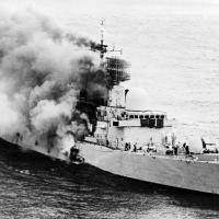 HMS Sheffield on fire after being struck by an AM 39 Exocet missile fired from an Argentine Super Étendard from a distance of 6 miles during the Falklands War. Sheffield later sank with a loss of 20 sailors. May 4, 1982