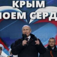 Russia's President Vladimir Putin (front) addresses the audience during a rally and a concert called