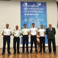 1T (EN) Adriano Palermo Silva e 1T (EN) Juliano Maia Ismério (segurando os certificados de conclusão) concluem o curso da EMBRAER - Foto: MB