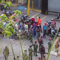 Funcionários militares e civis encapuzados reunidos em uma rua de Caracas,  19ABR17.