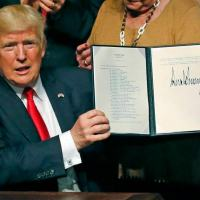 President Donald Trump signs his Cuba policy at the Manuel Artime Theater in Miami on Friday, June 16, 2017.