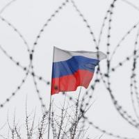 Bandeira russa na embaixada da Rússia em Kiev é vista por detrás de arame farpado