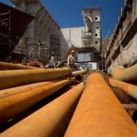 Operários que trabalham na manutenção de petroleiros inacabados no Estaleiro Mauá caminham sobre tubos enferrujados: crise financeira da Petrobras e escândalos de corrupção mergulharam indústria naval em nova crise - Márcia Foletto / Agência O Globo