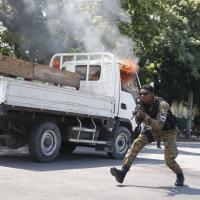 Guardas Presidenciais do Haiti tomam posição junto a veículo durante as manifestações dos funerais de duas vítimas mortas durante incidentes em Porto Príncipe.
