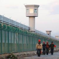 Trabalhadores caminham ao lado de cerca do que é oficialmente chamado de centro educacional de habilidades vocacionais em Dabancheng, na região chinesa de Xinjiang 04/09/2018 REUTERS/Thomas Peter