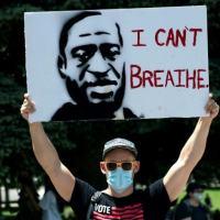Um manifestante com um cartaz em homenagem a George Floyd, 30 de maio de 2020 em Denver