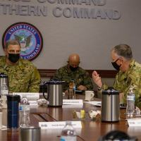 Military personnel hold a discussion with general Milley.
