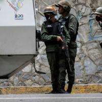Membros da Guarda Nacional da Venezuela se protegem atrás de um blindado durante enfrentamentos com supostos criminosos nos arredores da comunidade La Cota 905 em Caracas, 8 de julho de 2021