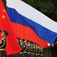 Militares chineses estendem bandeiras de China e Rússia durante solenidade em Pequim