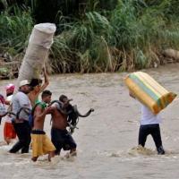 (Arquivo) Migrantes venezuelanos cruzam o rio Táchira em direção à Colômbia, em 19 de novembro de 2020
