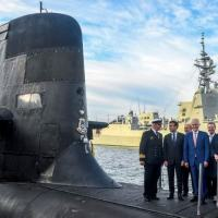 Foto de arquivo tirada em 2 de maio de 2018 mostra o presidente francês Emmanuel Macron (segundo da esquerda) com o então primeiro-ministro australiano Malcolm Turnbull (centro), de pé no convés de um submarino australiano, o HMAS Waller, em Sydney (AFP/BRENDAN ESPOSITO)