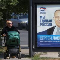 A woman walks past a campaign poster of Russian Foreign Minister Sergei Lavrov of the United Russia political party ahead of the Russian parliamentary and regional voting in Simferopol, Crimea, Sept. 15, 2021.