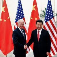 Joe Biden e Xi Jinping se cumprimentam durante encontro em Pequim em 2013